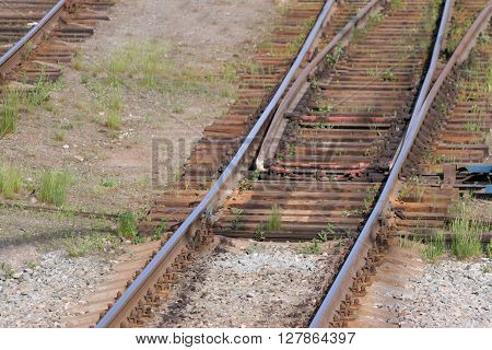 Close up view of railway with wooden sleepers grass and turnout