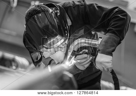 Industrial worker with protective mask welding inox elements in steel structures manufacture workshop. Black and white photo. poster