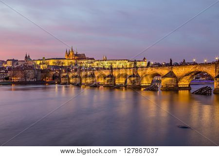 Charles Bridge in Prague towards the Lesser Quarter and Prague Castle at sunset.
