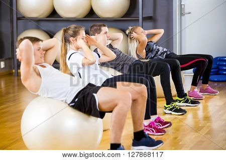 Focused team doing sit ups on bosu ball and at the fitness class. Core muscle and balance workout. Team and motivation at the gym.