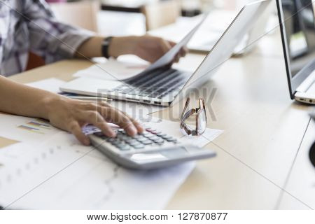 Woman Working With Calculator, Business Document And Computer Notebook
