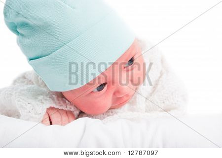 The Newborn Child In A Blue Hat On A Pillow