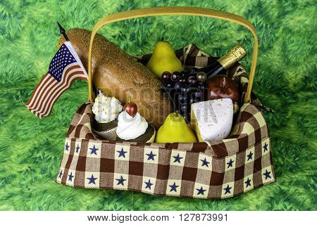 picnic basket of fruits bread cheese wine cupcakes and American flag on green background