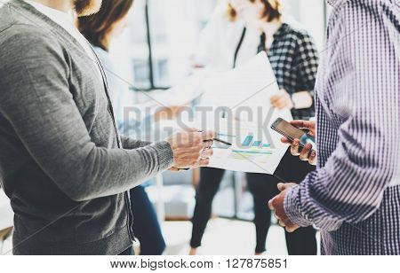Business meeting office.Closeup photo documents holding hands. Photo account managers crew working with new startup project.Idea presentation, analyze marketing plans.Blurred, film effect.