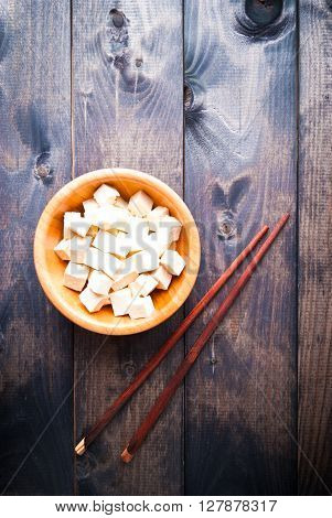 Bowl of raw tofu cubes and chopsticks on shabby wooden background. Space for text