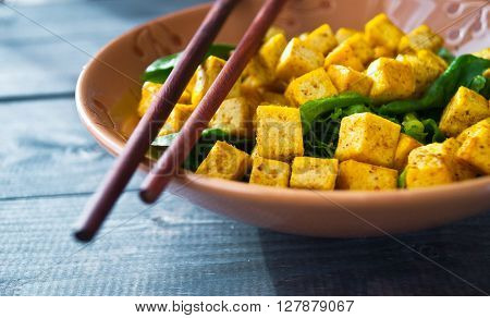 Salad from fried tofu with curry and fresh spinach in brown bowl with chopsticks as food background