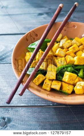 Salad from fried tofu with curry and fresh spinach in brown bowl with chopsticks. Close up