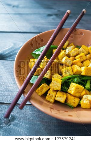 Salad from fried tofu with curry and fresh spinach in brown bowl with chopsticks. Asian cuisine