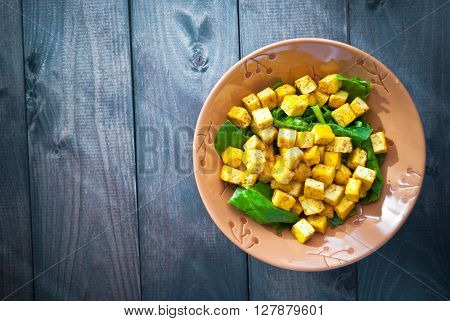 Salad from fried tofu with curry and green leaves of fresh spinach in brown bowl. Space for text