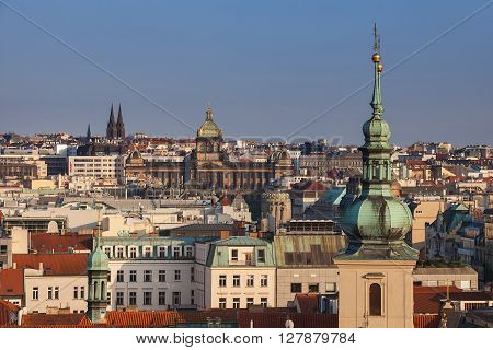 Aerial view of the traditional red roofs of the city of Prague, Czech Republic with the towers of St. Havel church and the National museum in the background.