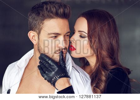 Sexy woman in gloves and red lips with young lover indoor seduction