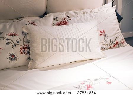 White Cozy Bed with Five Comfortable Soft Vintage Pillows.