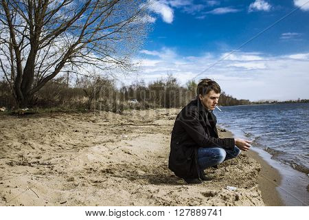 The man on the beach in the thoughts of his beloved, with a cigarette, trenchcoat, sand and sun, a leafless tree