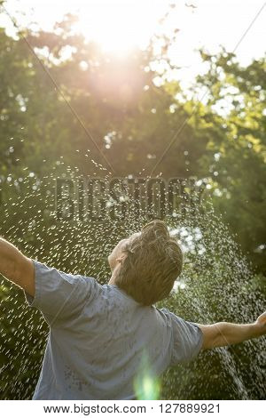 Young mam standing under a spray of water on a hot day with his arms outstretched rejoicing leafy green tree background.
