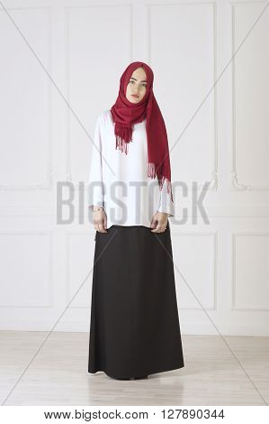 Studio photo of a beautiful young woman eastern type full-length, on a light background, dressed in the Muslim style