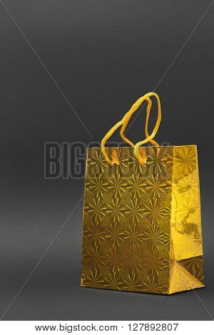 Shiny yellow gift bag isolated on a black background