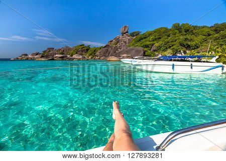Close Up of tanned legs of woman on a speedboat while admiring the spectacular views of Koh Similan Island No.8 with Sail Rock landmark in Similan National Park, Phang Nga, Thailand.