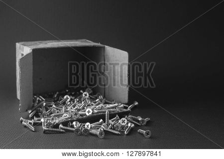 Screws located on a black background to understand an industrial concept