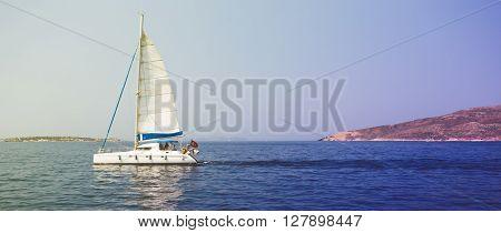 Sailing boat floating on blue sea near island
