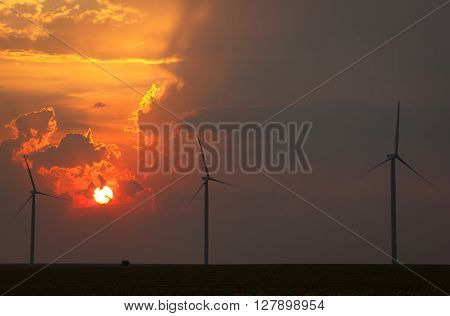 Sunflower field and wind turbines at sunset. Vintage effect.