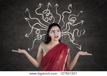 Portrait of Indian woman thinking a solution while wearing sari clothes with arrow on the blackboard