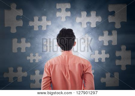 Image of a young businessman looking at puzzle. Business solution concept