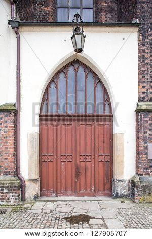 Old wood doors to cathedral. Lantern above.