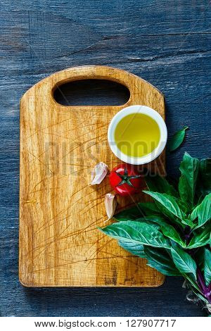 Fresh butch of thai basil and tomatoes with olive oil on rustic wooden cutting board over dark background top view. Vegetarian food cooking concept.