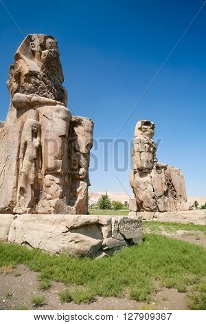 giant double statue of landmark Egyptian pharaoh Amenhotep III named The Colossi de Memnon public sculpture monument in Luxor Egypt Africa