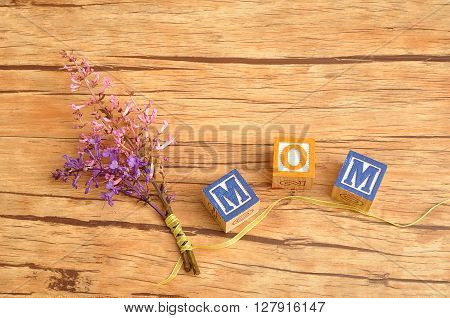 Mom spelled with colorful alphabet block displayed with a bunch of pink and purple flowers that is tied togehter with a yellow ribbon
