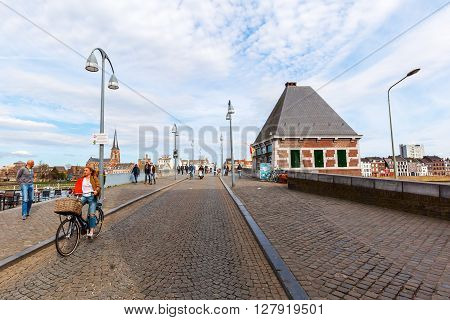 Maastricht Netherlands - April 11 2016: bridge over the river Meuse in Maastricht with unidentified people. Maastricht is a university city and the capital of the Dutch province Limburg