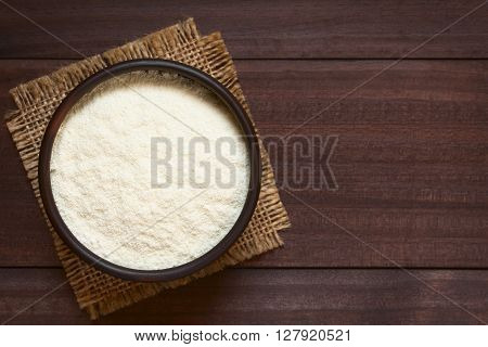 Powdered or dried milk in bowl photographed overhead on dark wood with natural light (Selective Focus Focus on the top of the milk powder)