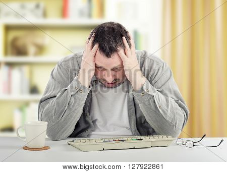 Mental disordered man is sitting at white desk. The middle-aged man holds his head in his hands. He wears a grey shirt and looks down on keyboard on the desk. There are white cup, glasses and rooms unfocused background.
