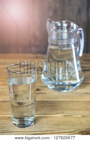 A glass and a carafe of the purest water on a wooden table. Rustic style