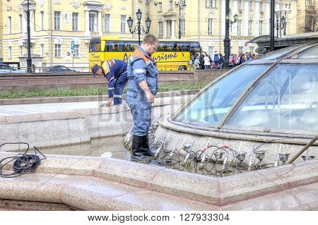 MOSCOW RUSSIA - April 24.2016: Worker of municipal service of city does the prophylaxis of sprayers of fountain
