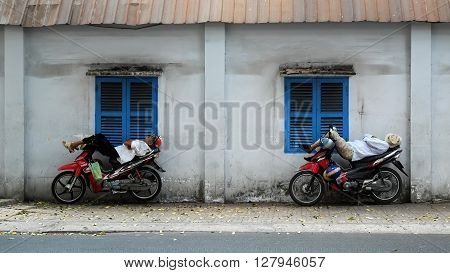 Vietnamese Motorbike Taxi Driver Sleeping On Motorcycle