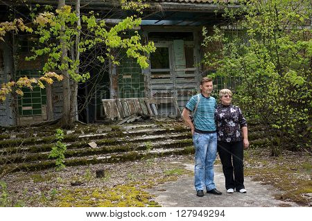 Pripyat, Ukraine - May 9, 2011: Evacuated couple poses for photo in front of their home school in Pripyat, Chernobyl Exclusion Zone, place of Chernobyl nuclear disaster. Every year on May 9 evacuated people are allowed to visit their former homes.