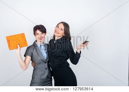 Two business women standing and embracing each other joyfully waving hands holding a tablet and phone