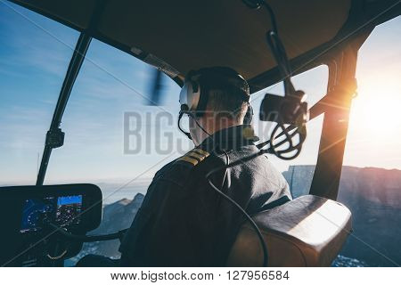 Rear view of a male wearing headphones flying a helicopter. Pilot flying an aircraft.