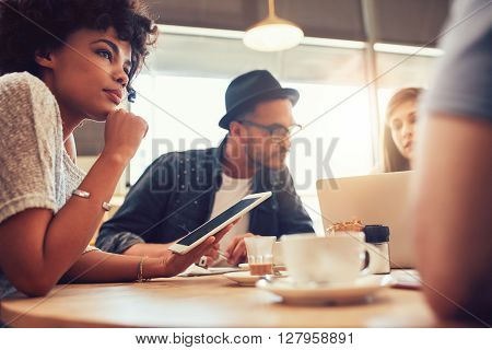 Close up portrait of african woman with digital tablet and people in background at a cafe table. Young friends sitting at a coffee shop with laptop and digital tablet.