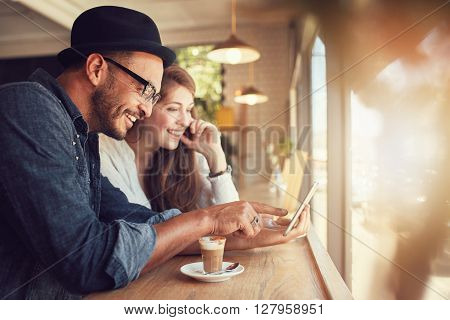 Smiling young couple in a coffee shop using touch screen computer. Young man and woman in a restaurant looking at digital tablet.