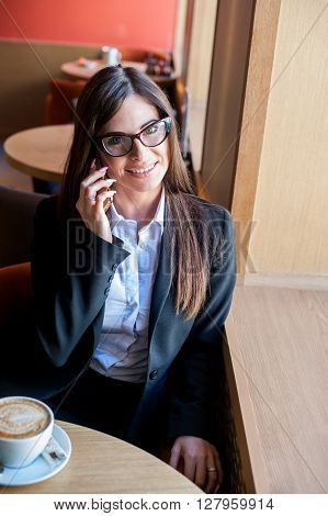 Young woman at cafe drinks coffee and talking on the mobile phone