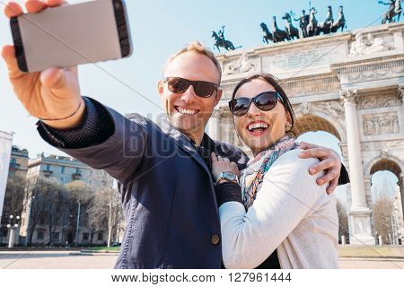 Happy couple take a selfie photo on the Arch of Peace in Milan