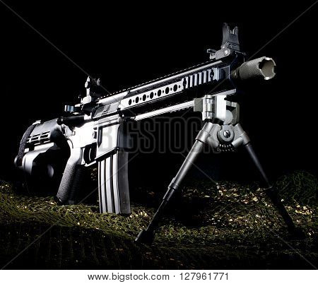 AR-15 style handgun on green netting with a dark background