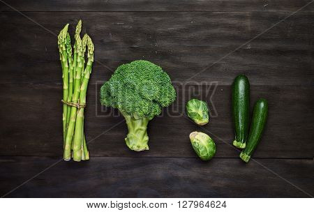 Fresh green organic vegetables on black wooden vintage table.Top view