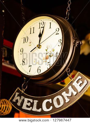 Hanging retro clock with welcome banner hanging