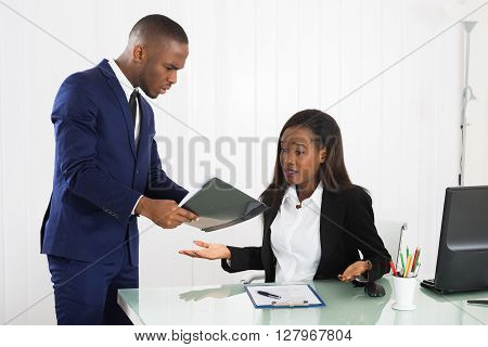 Unhappy Young Boss Showing Document To Her Female Worker In Office