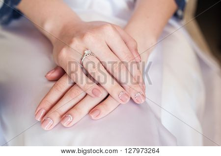 Bride hand with manicure on wedding dress.