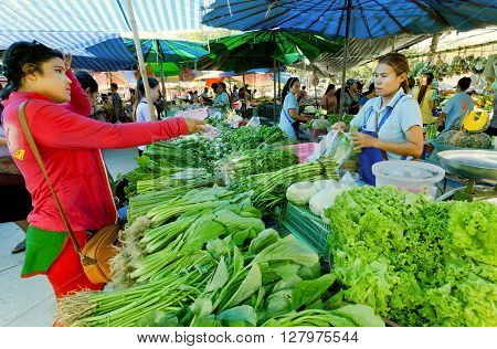 PHUKET, THAILAND - MAR 7, 2016: Woman buying green vegetables at village market with fresh farmers food on March 7, 2016. First written mention about the buddhist monastery belongs to 1837