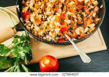 Cooked vegetables and mushrooms in frying pan with red tomato and green leaf